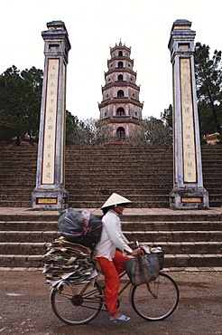 Woman on bicycle in front of Thien Mu Pagoda, Hue, Vietnam, Indochina, Southeast Asia, Asia