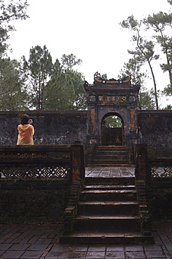 Tourist photographing Dai Hong Mon, Minh Mang Tomb, Hue, Vietnam, Indochina, Southeast Asia, Asia