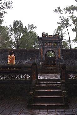 Tourist photographing Dai Hong Mon, Minh Mang Tomb, Hue, Vietnam, Indochina, Southeast Asia, Asia