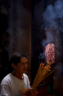 Man with joss sticks, Hue, Vietnam, Indochina, Southeast Asia, Asia