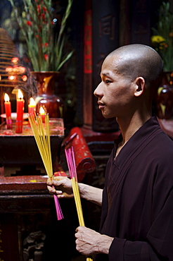 Monk with joss sticks during ceremony in a Buddhist temple, Ho Chi Min City, Vietnam, Indochina, Southeast Asia, Asia