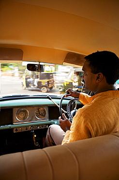 Kerela 1950's Ambassador car with driver, busy Keralan street through windscreen, India, Asia