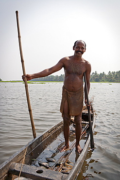 Fisherman standing in boat with fish, Kerala, India, Asia
