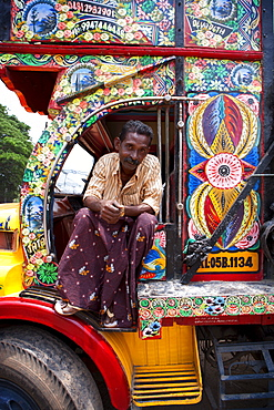 Kerelan driver sitting in cab of brightly decorated lorry, Kerala, India, Asia