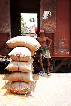Depot worker unloading rice sacks from train, Kerala, India, Asia