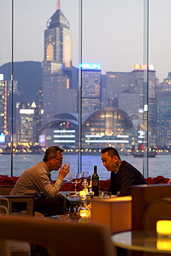 Businessmen drinking in hotel bar at dusk, Hong Kong, China, Asia