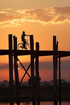 Cyclist on the U Bein teak bridge at sunset, Amarapura, Mandalay, Myanmar (Burma), Asia