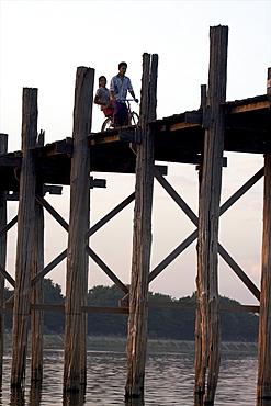 Cyclist on the U Bein teak bridge, Amarapura, Mandalay, Myanmar (Burma), Asia