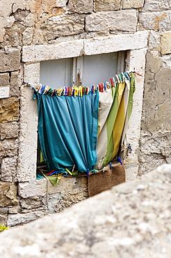 Stone window frame with hanging washing in Dubrovnik, Croatia, Europe