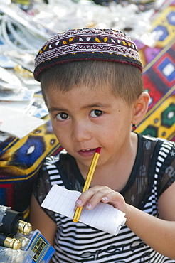 Young boy with pen in his mouth, Khiva, Uzbekistan, Central Asia, Asia