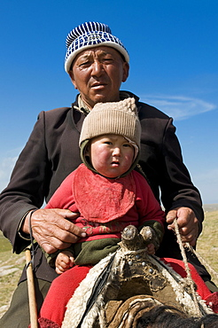 Grandfather with his grandson riding a horse, Song Kul, Kyrgyzstan, Central Asia, Asia