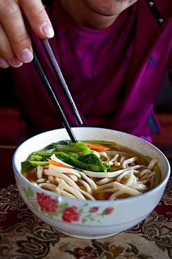 Woman eating noodle soup, Lhasa, Tibet, China, Asia
