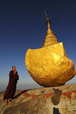 Monk praying on Kyaiktiyo Pagoda known as golden rock on top of Mount Kyaiktiyo, Myanmar, Asia