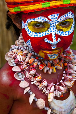 Colourfully dressed and face painted local child celebrating the traditional Sing Sing in the Highlands of Papua New Guinea, Pacific