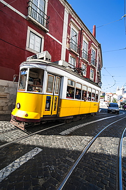 Famous tram 28 going through the old quarter of Alfama, Lisbon, Portugal, Europe