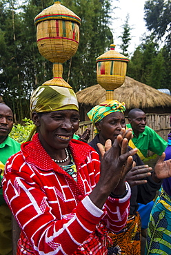 Women carrying baskets on their heads at a ceremony of former poachers, in the Virunga National Park, Rwanda, Africa