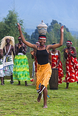Woman carrying a basket on her head at a ceremony of former poachers, in the Virunga National Park, Rwanda, Africa
