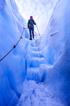 Woman walking steps out of a ice cave in Fox Glacier, Westland Tai Poutini National Park, South Island, New Zealand, Pacific