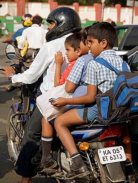Travelers crowd onto motorcycles on the road in Bangalore, Karnataka, India