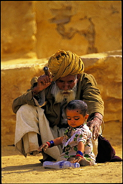 Old man taking care of a child in the surroundings of Thar Desert, Rajasthan, India