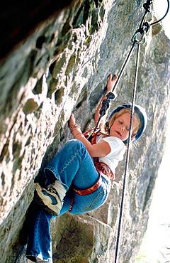 Young girl climbing rock face at rock climbing school
