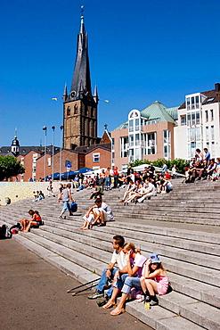 Germany, North Rhine Westphalia, Dusseldorf, People sitting on the stairs by the castle tower at the Rheinuferpromenade along the Rhine river