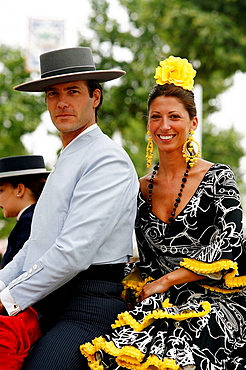 Couple wearing traditional costumes sitting on a horse at the April Fair, Seville, Spain