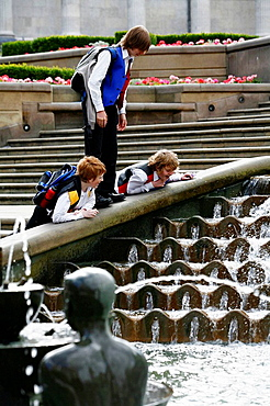 Children playing by the fountain below the Council House in Victoria Square, Birmingham, England, UK