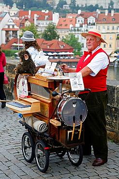 Man playing a traditional music box on Charles bridge, Prague, Czech Republic