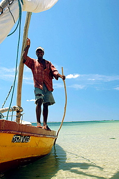 Fisherman standing on the side of his dhow with the turquoise sea and the blue sky in the background, Ilha de Mocambique (Island of Mozambique), Mozambique, Southern Africa