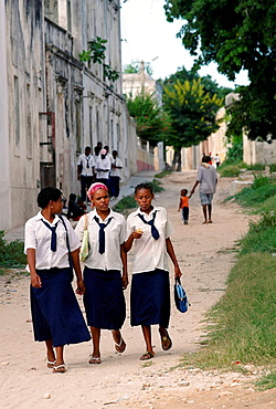 Full body image of three young school girls in school uniform with white shirt, knee-length skirt and blue tie walking down a sandy backstreet in Ilha de Mocambique (Island of Mozambique), Mozambique, Southern Africa