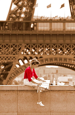 Woman reading newspaper on the Trocadero in front of the Eiffel tower, Paris, France