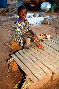 Lobi child playing balafon (typical Lobi instrument), Gaoua area, Lobi Country, Burkina Faso