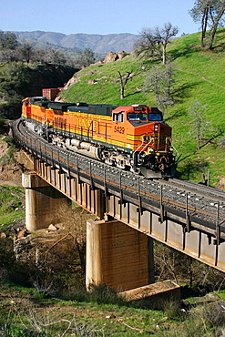 Burlington Northern Santa Fe Train crossing over an old bridge from the 1800s traveling from Bakersfield heading to Tehachapi in the early morning hours, Union Pacific train traveling in through Tehachapi towards Mojave Desert, California, USA