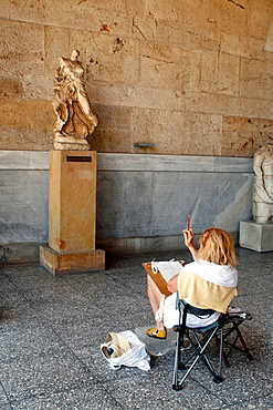Designer in front of a statue in the Ancient Agora Museum (Stoa of Attalos), Athens, Greece