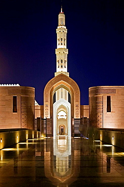 Architectural detail of the entrance courtyard and arch leading to the main prayer hall of the Sultan Qaboos Grand Mosque, with a minaret in the background, at night, Ghubrah, Muscat, Oman