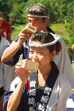 Drinking Sake out of a traditional square wooden cup to mark the opening of the Japanese Festival, an annual event at the Missouri Botanic Garden in St, Louis, Missouri, USA