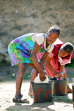 Young girls washing clothes in a bucket, Maputo, Mozambique