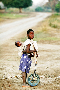 Child with his brother and a self-made toy, Mozambique