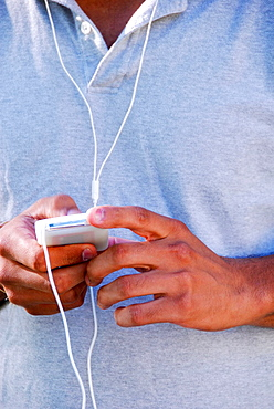 young male ethnic adult using music device