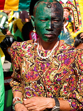 Man in green face and colorful dress, all part of the wacky Ati Atihan Festival, Kalibo, Philippines