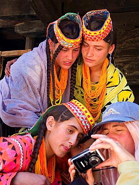 Kalasha women looking at their photos, Pakistan