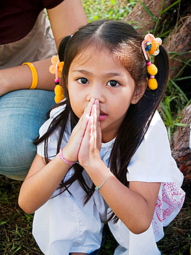 Young girl with hands folded in prayer at the Vegetarian Festival, Phuket, Thailand