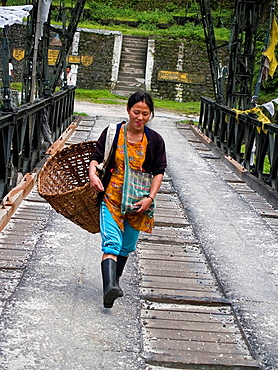 Girl with her basket crossing a bridge in Sikkim India