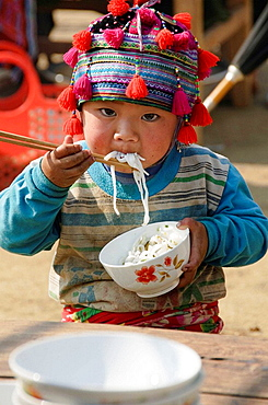 Hmong boy stuffing his face with noodles at market in Tam Duong near Sapa Vietnam