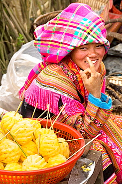 colorful Flower Hmong woman selling pineapples in the market in Cau Son near Bac Ha Vietnam