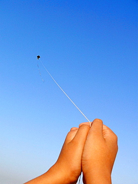 Hand and kite in flight, a boy playing with a kite  Pune, Maharashtra, India