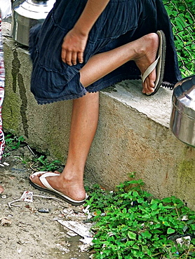 A girl is standing with folding her one leg near community water tap, low section  Pune, Maharashtra, India
