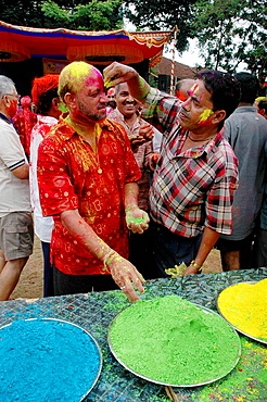 Panjim Goa, India, men putting colored powder on their faces during the Holi feast - 817-193969