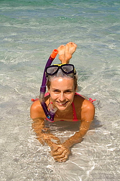 Portrait of woman wearing a snorkel, lying in shallow water, Fraser Island, Australia